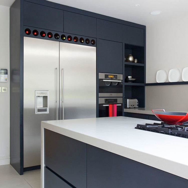 Dark kitchen design with stainless double wall oven next to stainless refrigerator